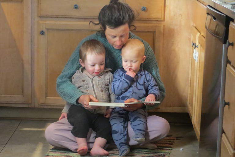 Woman holding two infants on the kitchen floor reading a book to them